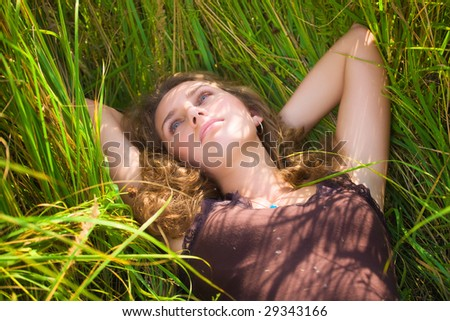 Young woman resting in a high summer grass.