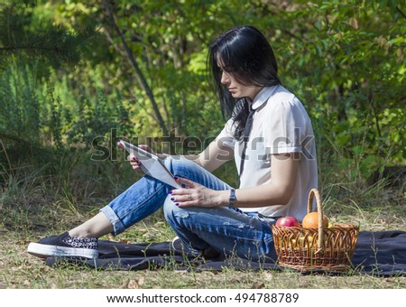 Young woman resting in a park on the lawn with her white tablet computer   basket of fruit
