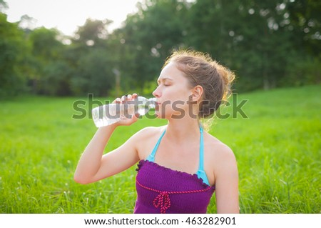 Young woman resting in a park. The girl drinks water from a bottle. Summer.