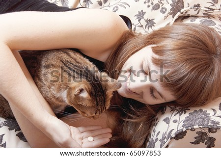 Young woman resting on a sofa with a little cat - stock photo