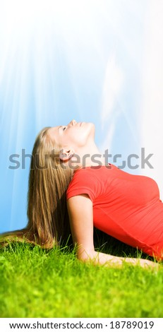Young woman resting on green grass. Bright sunshine effect. - stock photo