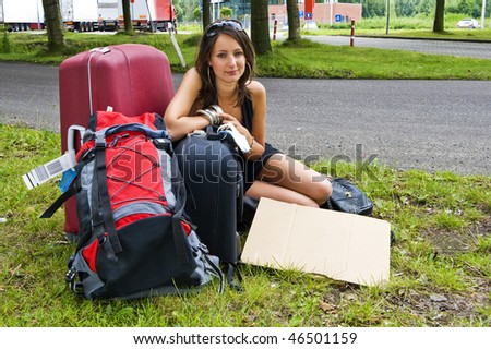 Young woman, resting on her bags, resting at a highway parking lot on her journey - stock photo