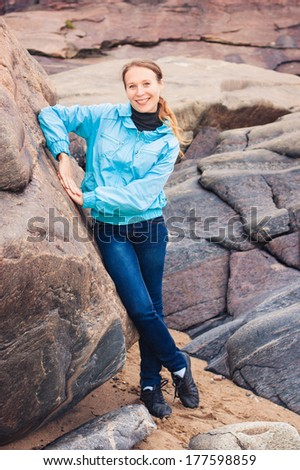 Young woman resting on the rocks. - stock photo