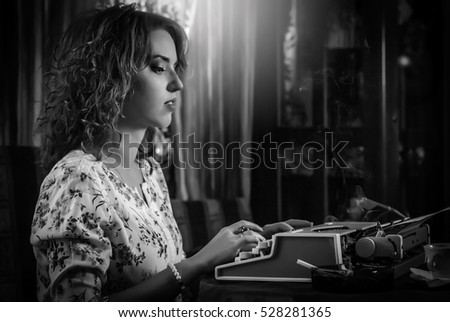 Young woman,retro look, sitting at a typewriter, portrait. Photo with noise. Black and white photo. Profile.