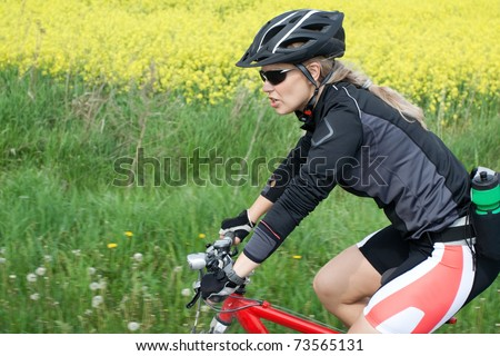 Young woman ride a bicycle on summer day - stock photo