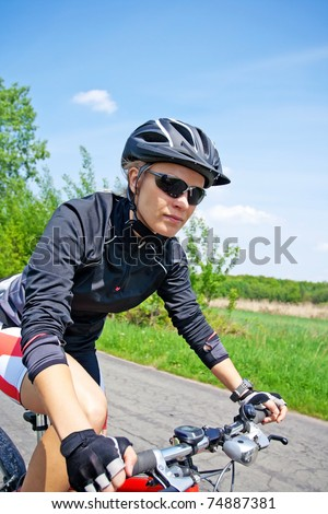 Young woman ride a mountain bike on summer day - stock photo