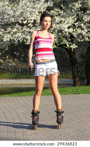 young woman ride rollerblades in the park