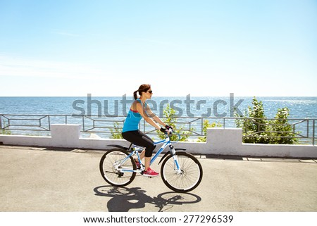 young woman riding a bike along the coast. Active people outdoors. sport lifestyle - stock photo