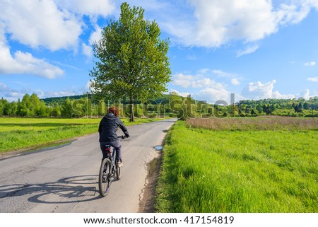 Young woman riding a bike on road along rural landscape near Krakow, Poland