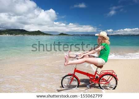 Young woman riding a bike on the beach