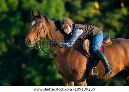 Young woman riding a horse, horse riding back. - stock photo