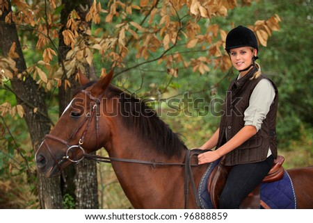 Young woman riding a horse through woodland - stock photo
