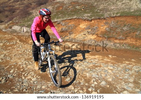 Young woman riding a mountain bike on rocky road