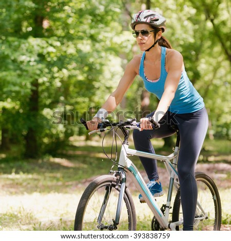 Young woman riding bicycle in park - stock photo