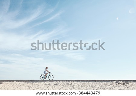 Young woman riding bicycle with basket against blue sky during summer - healthy lifestyle concept - stock photo