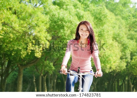 young woman riding bike and listening music - stock photo