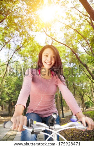 young woman riding bike and listening music on the forest trail - stock photo