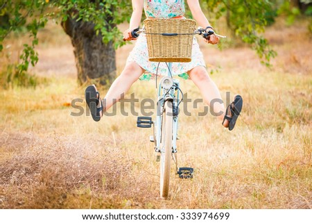 young woman riding bike in a country road - stock photo