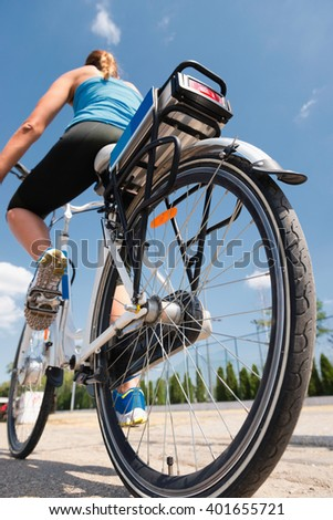 Young woman riding e-bike or electric bicycle - stock photo