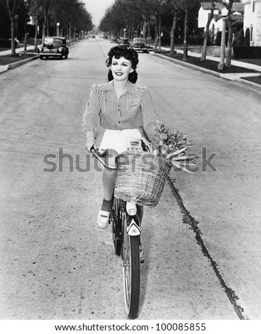 Young woman riding her bicycle with basket full of flowers and carrots - stock photo
