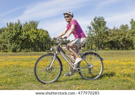 Young woman riding her bike on a meadow