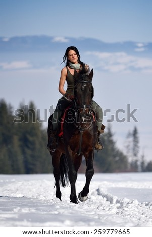 young woman riding horse outdoor in winter - stock photo