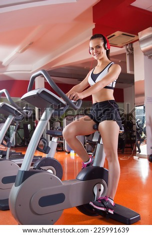 young woman riding on a bicycle- gym fitness
