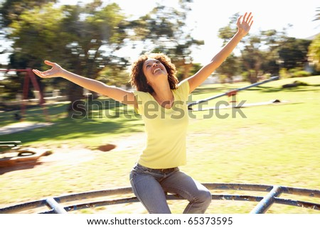 Young Woman Riding On Roundabout In Park - stock photo