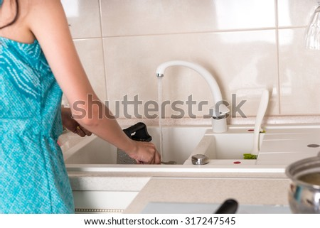 Young woman rinsing a cheese grater under running water in the sink in the kitchen as she prepares the evening meal - stock photo