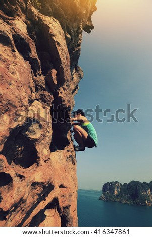 young woman rock climber climbing at seaside cliff