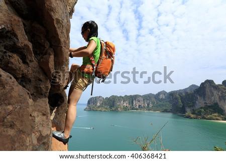 young woman rock climber climbing at seaside mountain cliff - stock photo
