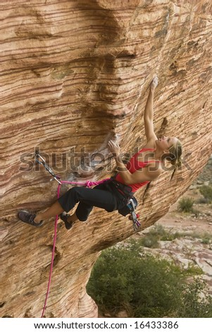 Young woman rock climbing in The Calico Hills, in Red Rock, Nevada. - stock photo