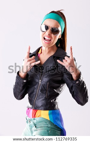 young woman rocker wearing leather jacket and sunglasses, screaming and making rock and roll hand gesture - stock photo