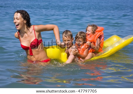 young woman rolls three children on an inflatable mattress in sea - stock photo