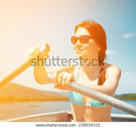 young woman rows the boat (filtered) - stock photo