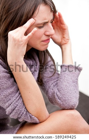 young woman rubbing against her temples because she has a bad headache - stock photo