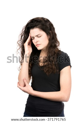 Young woman rubs the temple area of her head as she winces her face in pain from a migraine headache. - stock photo