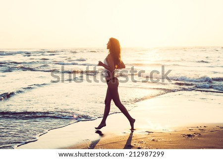 young woman run along sandy beach at sunset, full body shot