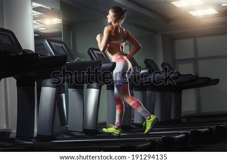 Young woman run on on a machine at the gym - stock photo