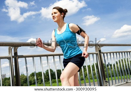 Young woman runing in the city over the brige in sun light, smiling. - stock photo