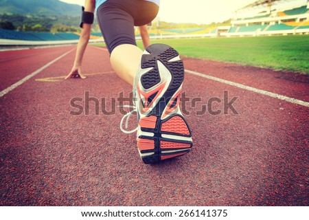 young woman runner getting ready for a run on track - stock photo