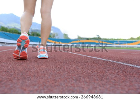 young woman runner legs running on track
