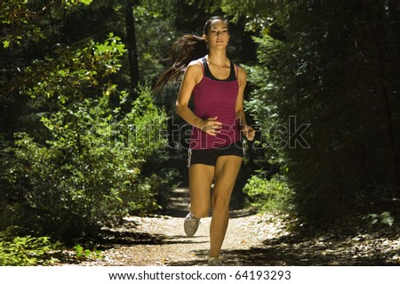 Young woman runner on forest trail - stock photo