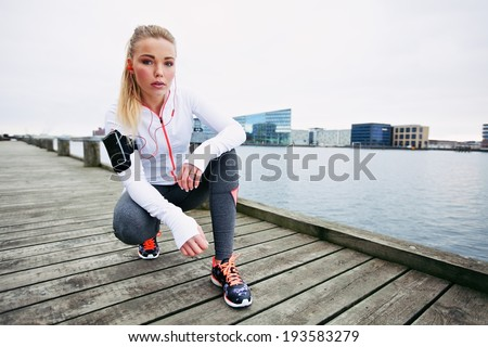 Young woman runner resting after running workout. Female fitness model crouching on sidewalk along river. Female jogger taking a break. - stock photo