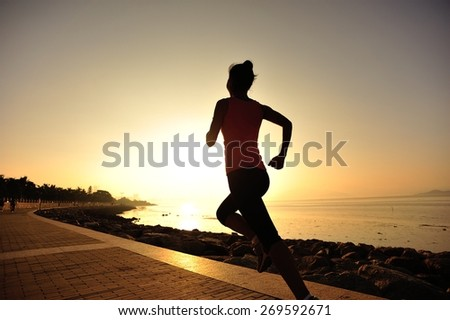 young woman runner running at seaside. woman fitness silhouette sunrise jogging workout wellness concept.