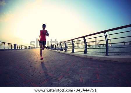 young woman runner running at the sunrise seaside - stock photo