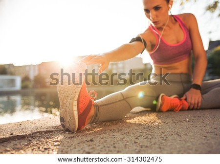 Young woman runner stretching legs before doing her summer workout. Sportswoman warming up before outdoor workout. - stock photo