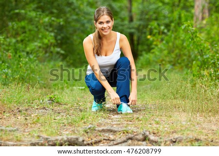 Young woman runner ties laces on a footpath in the wood.