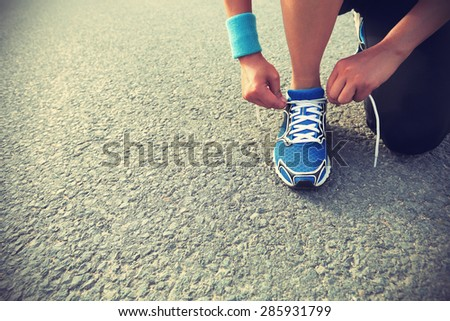 young woman runner tying shoelaces on city road - stock photo