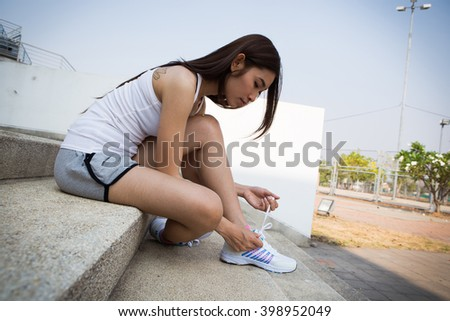 young woman runner tying shoelaces on stairway